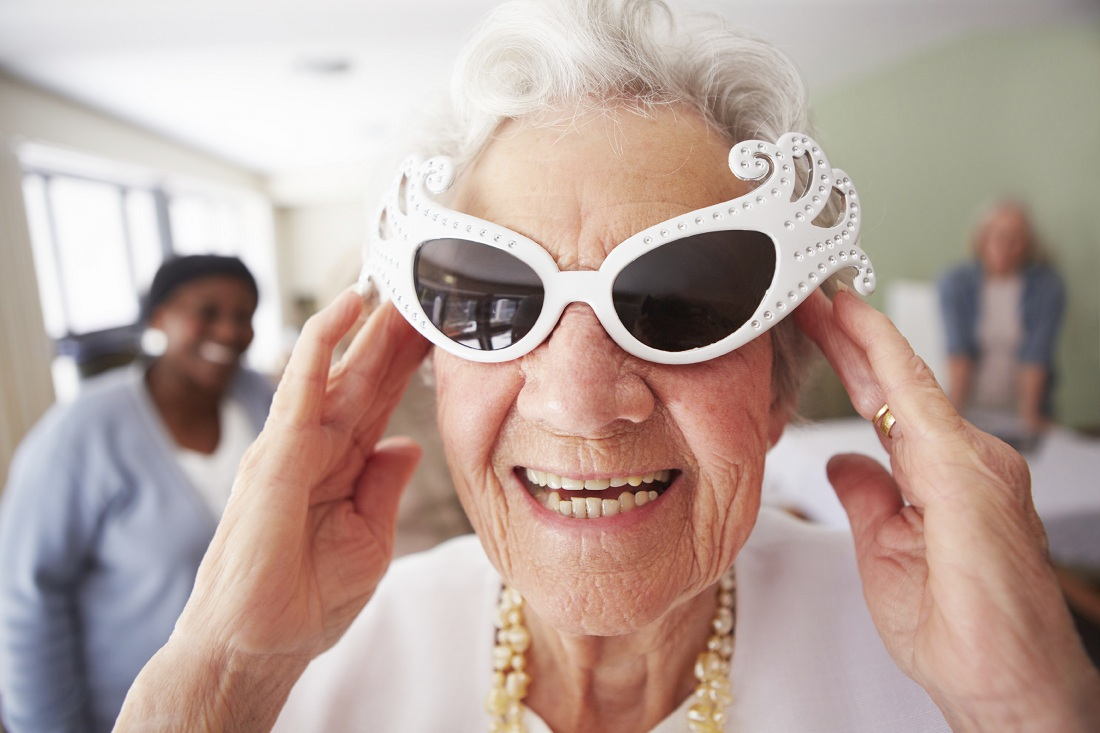 An elderly woman wearing funky sunglasses while standing in a nursing home
